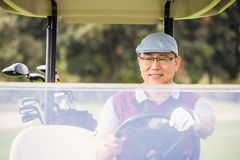 Golfer driving a golf buggy Stock Images