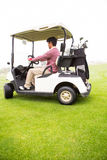 Golfer driving in his golf buggy Royalty Free Stock Photography