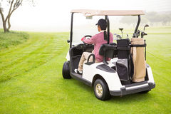 Golfer driving in his golf buggy Stock Photography