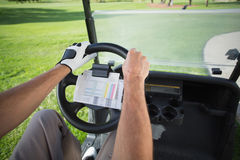 Golfer driving his golf buggy forward Stock Image
