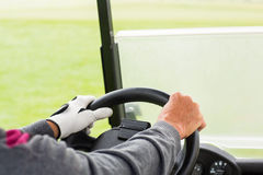 Golfer driving his golf buggy forward Royalty Free Stock Image