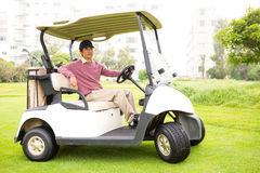 Golfer driving his golf buggy looking at camera Royalty Free Stock Photography