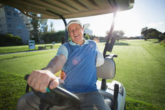 Golfer driving his golf buggy and smiling at camera Stock Photos