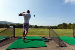 Golfer at the Driving Range. Athletic golfer swinging at the driving range dressed in casual attire Stock Images