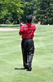 Golfer on Fairway. A rear view of a male golfer completing golf drive from fairway Stock Photo