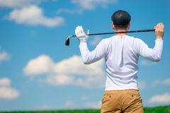 Golfer in a field with a golf club on his shoulders resting after a successful game stock photo