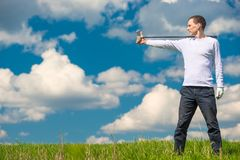 Golfer in the field with a stick for playing golf on the right,. On the left is a stretch for the inscription royalty free stock image