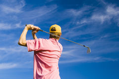 Golfer finishing his swing Royalty Free Stock Image