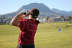 Golfer Follow Throug. Follow Through of a young professional golfer whilst practising on the range Stock Photography