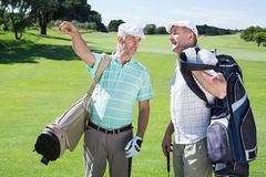 Golfer friends chatting and holding their golf bags Stock Image