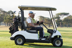 Golfer friends sitting in golf buggy Royalty Free Stock Photography