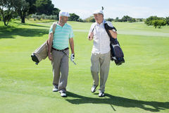 Golfer friends walking and chatting Royalty Free Stock Photo