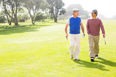 Golfer friends walking and chatting Royalty Free Stock Images