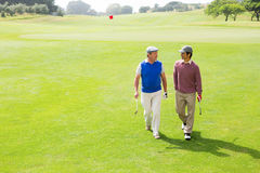 Golfer friends walking and chatting Royalty Free Stock Photos
