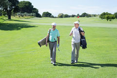 Golfer friends walking and holding their golf bags Royalty Free Stock Photos