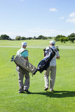 Golfer friends walking and holding their golf bags Royalty Free Stock Photography