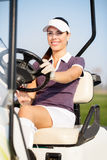 Golfer in golf cart. Smiling female golfer driving  golf cart Stock Images
