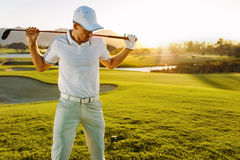 Golfer with golf club at course on a summer day. Shot of male golfer with golf club at course on a summer day. Young man holding a golf club and looking down Stock Image