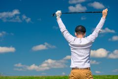 A golfer with a golf club is pleased with his victory, the view. From the back Royalty Free Stock Photography