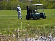 Golfer on Golf Course with Golf Cart. Golfer Swinging Club with Golf Cart on Golf Course stock images