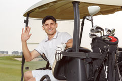 Golfer in golfcart with his clubs Stock Images