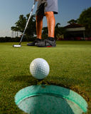 Golfer golfing and close-up of golf ball Stock Photo