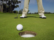 Golfer On Green With Ball At Hole In Foreground Stock Photography