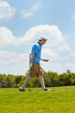 Golfer Happy with his Tee Shot. Young golfer content with his swing and placement of the ball down the fairway Royalty Free Stock Images