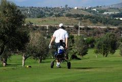 Golfer with his buggy, Caleta de Velez. Golfer walking along with his buggy at Los Llanos de Baviera Golf, Caleta de Velez, Malaga Province, Andalusia, Spain Stock Photos