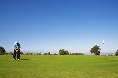 Golfer hitting the ball. A golfer playing golf on a green Royalty Free Stock Photography