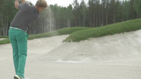Golfer Hitting Ball with Club on Beautiful Golf Course. Golfer hits an fairway shot towards the club house. Man hitting stock footage