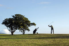 Golfer. Hitting the ball on the grass Royalty Free Stock Image