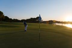 Golfer hitting ball to hole Royalty Free Stock Photo