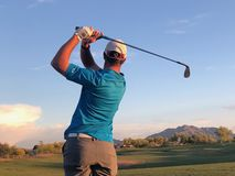 Golfer hitting a golf ball from a back view. Golfer hitting golf shot with a iron on course in Arizona stock photography