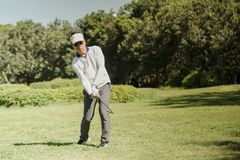 Golfer hitting golf ball on fairway green grass royalty free stock photography