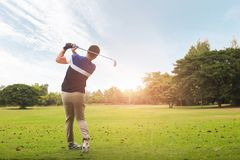 Golfer hitting golf shot with club on course at evening time. Golfer hitting golf shot with club on course at evening time stock photo