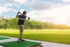 Golfer hitting golf shot with club on course at morning time.  stock photography