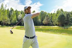 Golfer hitting golf shot with club on course while on summer vacation.  royalty free stock photos