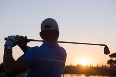 Golfer hitting long shot. With driver on course at beautiful sunset Royalty Free Stock Photo