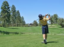 Golfer hitting a nice tee shot. Young golfer hitting a nice tee shot with a driver on a beautiful golf course Royalty Free Stock Photo