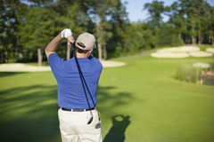 Golfer hitting onto defocused green. A golfer hits on to a green in the afternoon. Focus on golfer Stock Photo