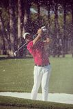 Golfer hitting a sand bunker shot. Golf player shot ball from sand bunker at course Royalty Free Stock Photo