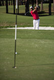 Golfer hitting a sand bunker shot. Golf player shot ball from sand bunker at course Royalty Free Stock Photos