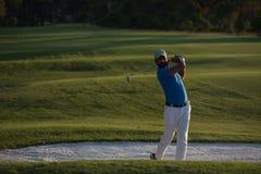 Golfer hitting a sand bunker shot on sunset. Golfer shot ball from sand bunker at golf course with beautiful sunset in background Stock Image