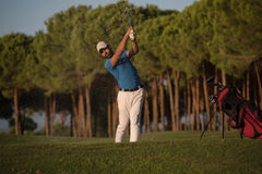 Golfer hitting a sand bunker shot on sunset. Golfer shot ball from sand bunker at golf course with beautiful sunset in background Royalty Free Stock Photography