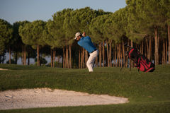 Golfer hitting a sand bunker shot on sunset. Golfer shot ball from sand bunker at golf course with beautiful sunset in background Stock Image