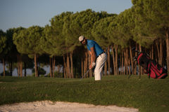 Golfer hitting a sand bunker shot on sunset. Golfer shot ball from sand bunker at golf course with beautiful sunset in background Stock Photo