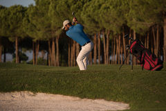 Golfer hitting a sand bunker shot on sunset. Golfer shot ball from sand bunker at golf course with beautiful sunset in background Royalty Free Stock Photos