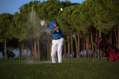 Golfer hitting a sand bunker shot on sunset Royalty Free Stock Image