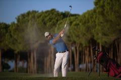 Golfer hitting a sand bunker shot on sunset. Golfer shot ball from sand bunker at golf course with beautiful sunset in background Stock Photo